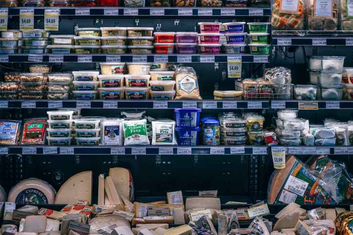 assorted cheese on grocery shelves